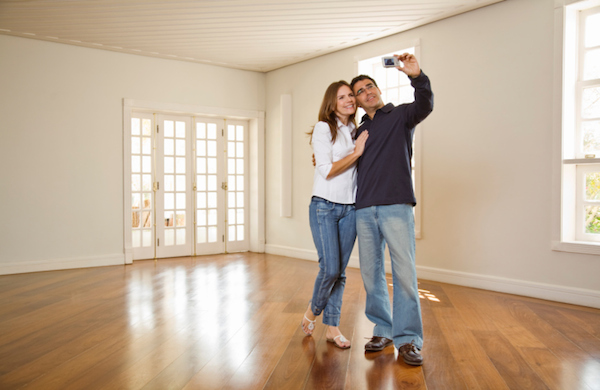 Couple using digital camera in empty room
